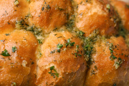 Buns of bread with garlic and herbs as background, closeup