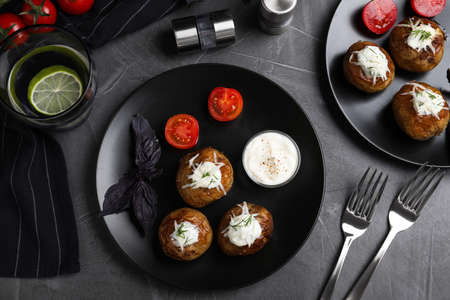 Delicious hot baked potato with sour cream dressing on grey table, flat lay