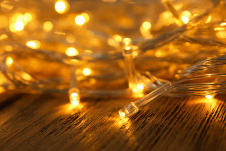 Glowing Christmas lights on wooden table, closeup view