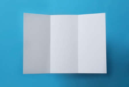 Empty flyer on blue background, top view. Mockup for design Stock Photo - 130134403