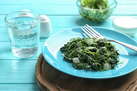 Tasty cooked spinach served on light blue wooden table. Healthy food