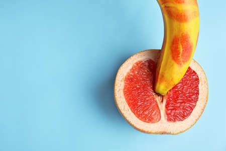 Platte lay compositie met verse banaan en grapefruit op blauwe achtergrond, ruimte voor tekst. Seks concept