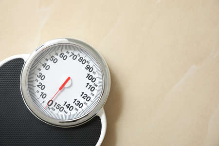 Top view of scales on floor, space for text. Overweight problem