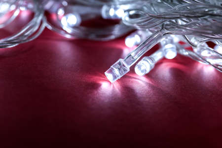 Glowing Christmas lights on burgundy background, closeup