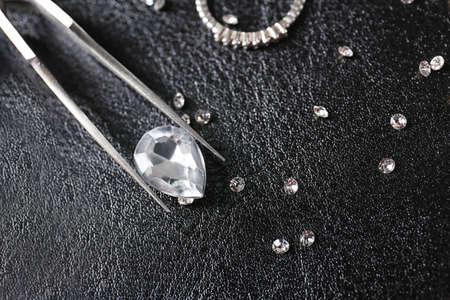 Jewels and tweezers on black leather surface 版權商用圖片