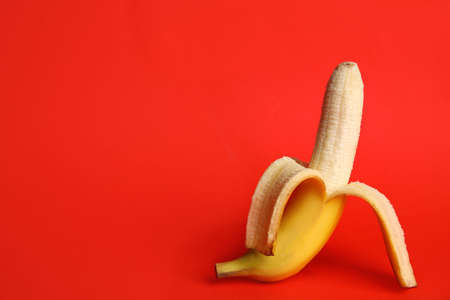Fresh banana on red background, space for text. Sex concept