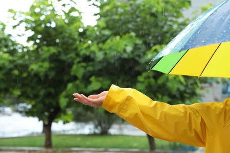 Woman with colorful umbrella outdoors on rainy day, closeup Banque d'images