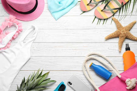 Flat lay composition with beach accessories on white wooden background, space for text Imagens