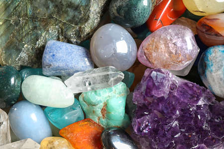Different beautiful gemstones as background, top view