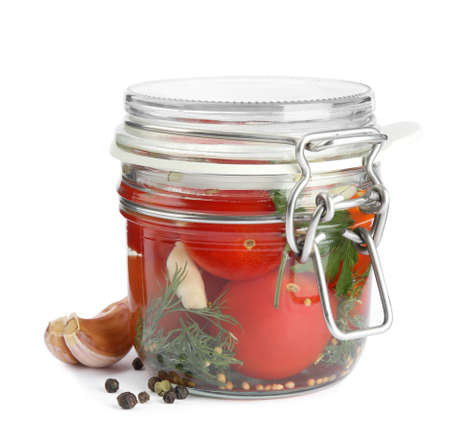 Pickled tomatoes in glass jar on white background