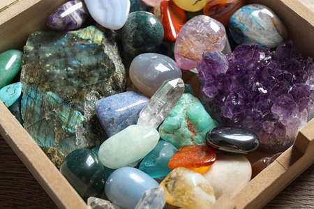 Box with different beautiful gemstones on table, closeup