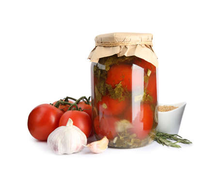Pickled tomatoes in glass jar and products on white background