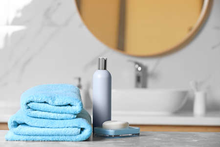Folded towels and toiletries on marble table in bathroom, space for text Stock Photo