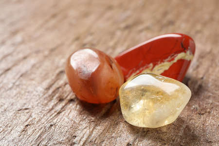 Beautiful red and white jade, carnelian agate and citrine quartz gemstones on textured surface Stock fotó