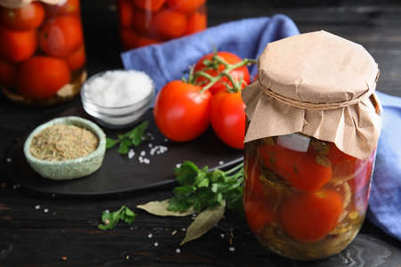 Pickled tomatoes in glass jars and products on black wooden table
