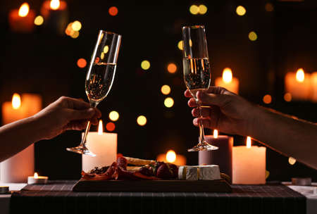 Young couple with glasses of champagne having romantic candlelight dinner at table, closeup Фото со стока - 130134362