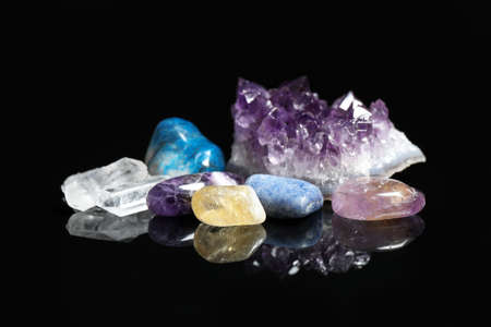 Pile of different beautiful gemstones on black background