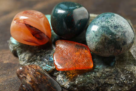 Different beautiful gemstones on table, closeup view