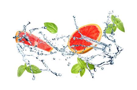 Jugosa toronja, albahaca y salpicaduras de agua sobre fondo blanco.