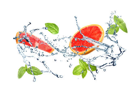 Juicy grapefruit, basil and splashing water on white background