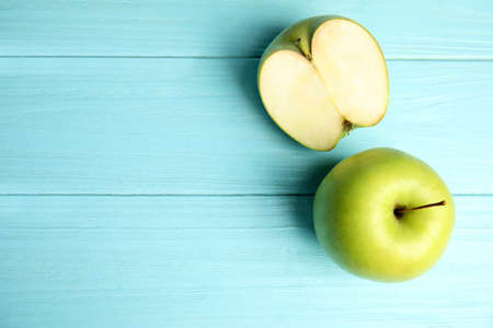 Flat lay composition of fresh ripe green apples on blue wooden table, space for text