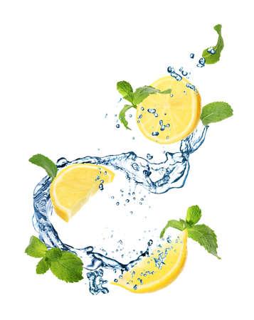 Jugoso limón, menta y salpicaduras de agua sobre fondo blanco. Foto de archivo