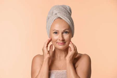 Ritratto di bella donna matura con pelle perfetta su fondo beige Archivio Fotografico