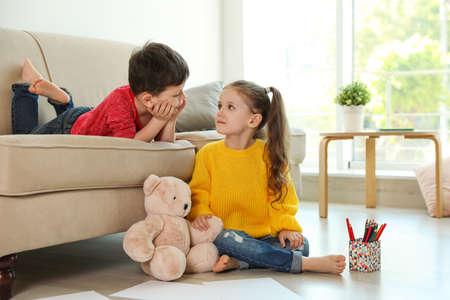 Schattige kleine jongen en meisje in de woonkamer Stockfoto