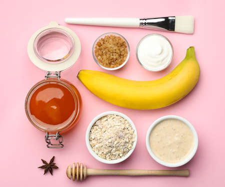 Different ingredients and handmade face mask on pink background, flat lay