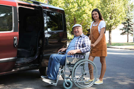 Young woman helping senior man in wheelchair to get into van outdoors
