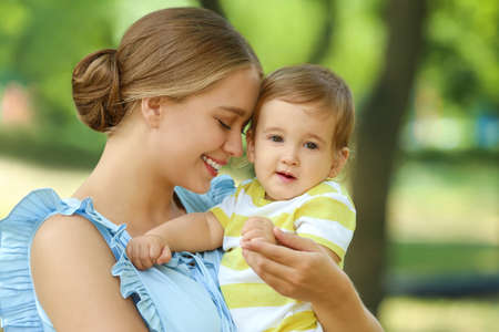 Beautiful mother with her cute baby in park on summer day Stock Photo