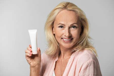 Ritratto di bella donna matura con pelle perfetta che tiene il tubo di crema su sfondo grigio