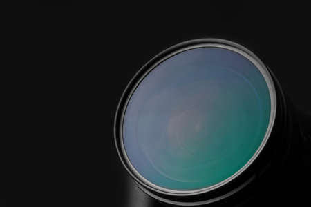 Modern camera on dark background, closeup of lens. Space for text