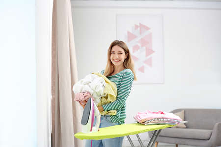 Young pretty woman holding heap of clean laundry near ironing board indoors