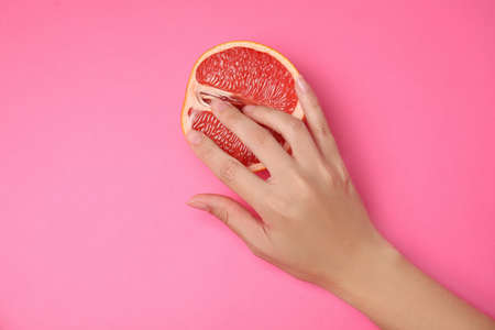 Young woman touching half of grapefruit on pink background, top view. Sex concept Zdjęcie Seryjne