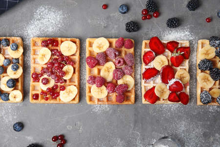 Flat lay composition with delicious waffles and fresh berries on grey table
