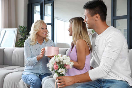Young couple with bouquet and gift box congratulating their mother in living room