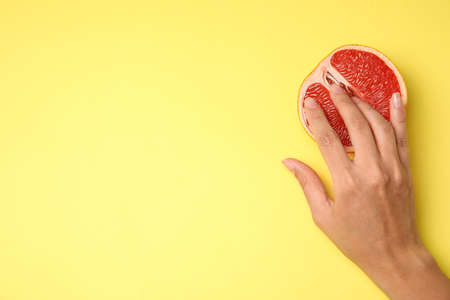 Young woman touching half of grapefruit on yellow background, top view with space for text. Sex concept