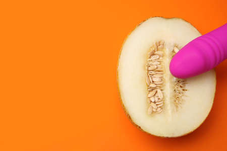 Half of melon and purple vibrator on orange background, flat lay with space for text. Sex concept Zdjęcie Seryjne