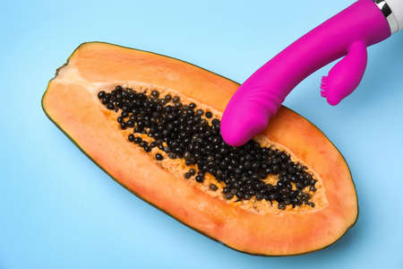 Half of papaya and purple vibrator on blue background, top view. Sex concept