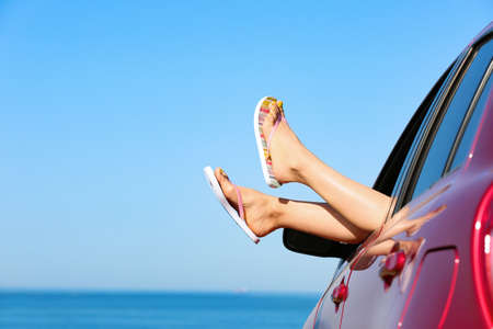 Closeup of woman showing legs with flip flops from car near sea, space for text. Beach accessories