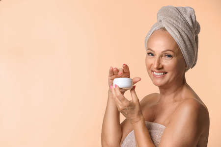 Portrait of beautiful mature woman with perfect skin holding jar of cream on beige background. Space for text Banco de Imagens