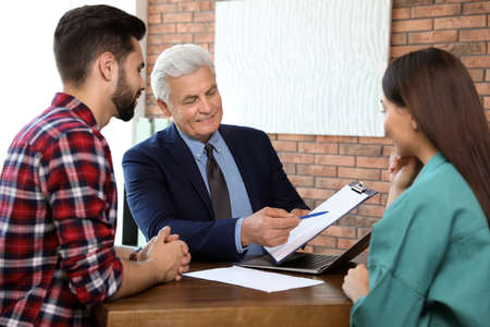 Senior notary working with young couple in office