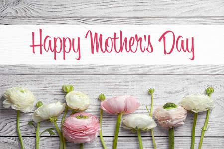 美丽的毛茛属花和文本愉快的母亲节在木背景,顶视图