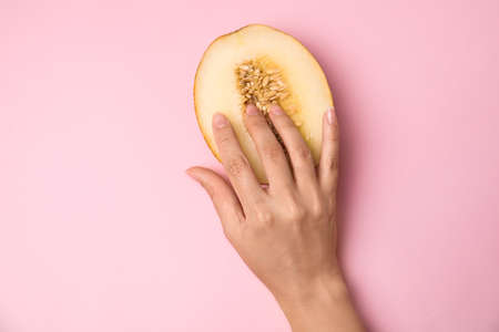 Young woman touching half of melon on pink background, top view. Sex concept