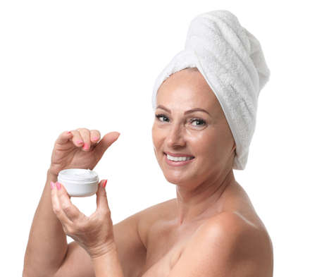 Portrait of beautiful mature woman with perfect skin holding jar of cream on white background Banco de Imagens