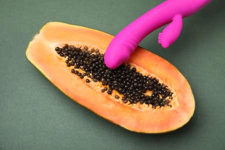 Half of papaya and purple vibrator on dark grey background, top view. Sex concept