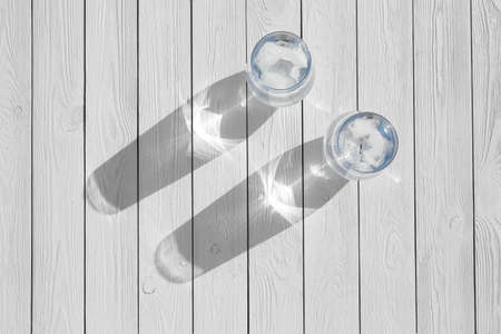 Glasses of refreshing drink with ice for hot summer day on wooden table, top view. Space for text