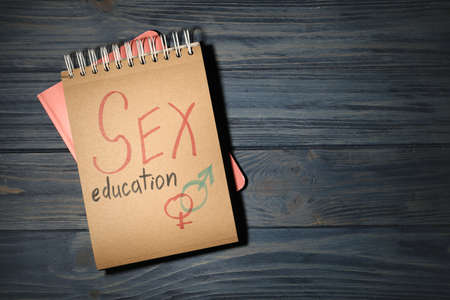 Notebook with phrase SEX EDUCATION and gender symbols on dark wooden background, top view. Space for text