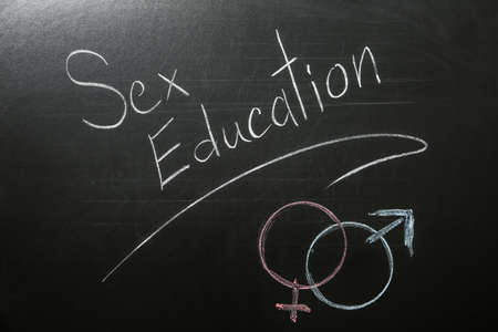 Gender symbols and phrase SEX EDUCATION written on black chalkboard